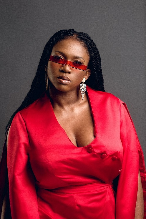 Waje Nigerian Musician wearing a red coloured dress with a red shade