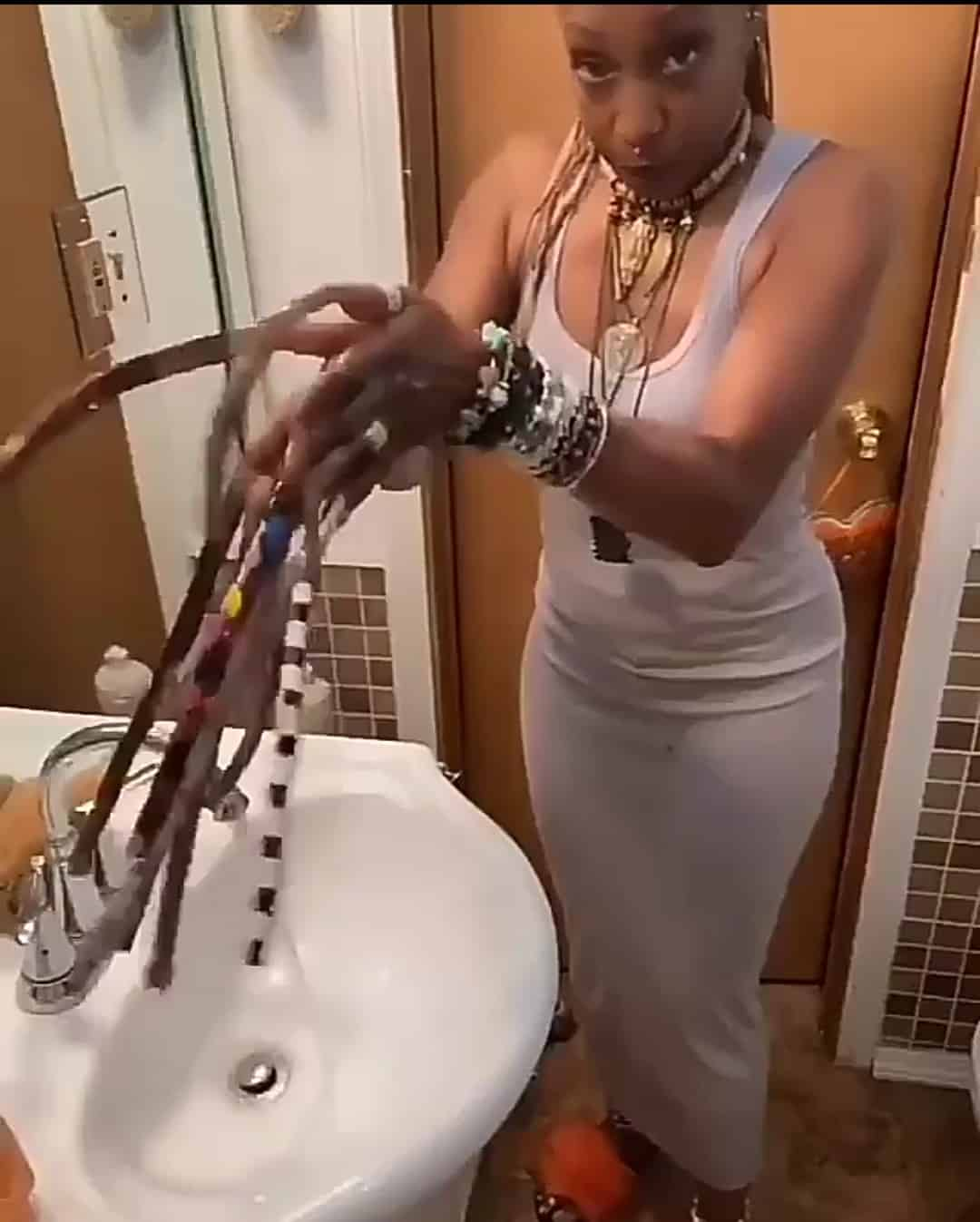 Woman with extremely long fingernails shows how she washes her hands