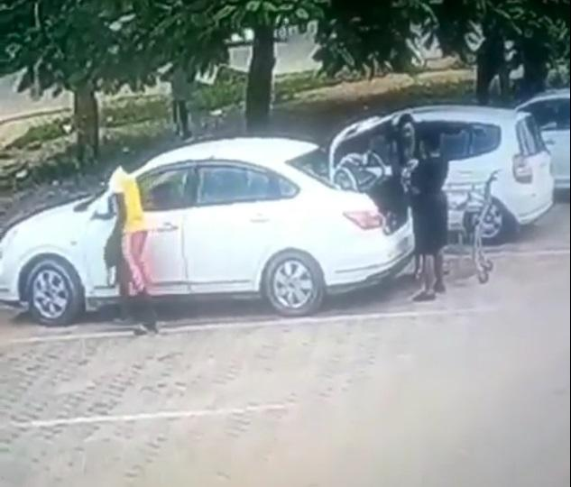 CCTV captures moment a young boy robbed a woman while offloading shopping bags in her trunk (Video)