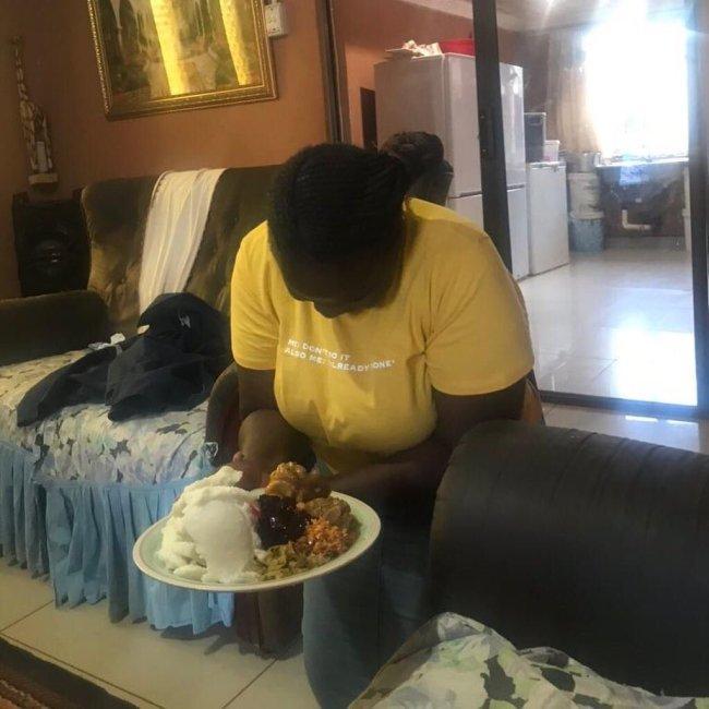 woman kneeling to serve husband food