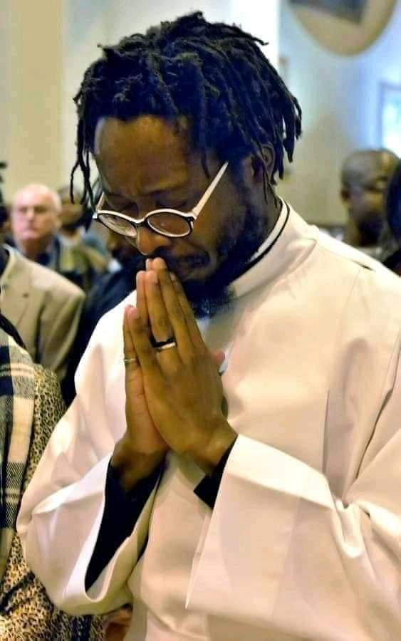 Man with dreadlocks as Catholic Priest
